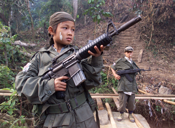 FILE PHOTO 31JAN00 - Samboo, a 12-year-old soldier in the Karen rebel army fighting against Myanmar's military government, poses with his gun in a jungle camp near the border with Thailand in this January 31 file picture, on the 51st anniversary of Karen revolution day. More than 300,000 child soldiers are fighting for national and guerillas armies around the world, according to the Coalition to Stop the Use of Child Soldiers in an interview May 10. JIR   BEST QUALITY AVAILABLE - RTR3ZGR