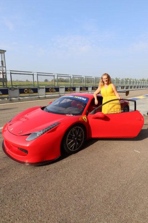posing with red ferrari car